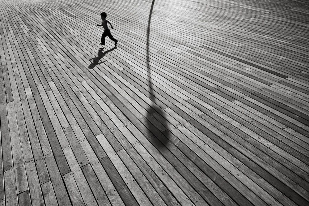 a small child running on a wooden boardwalk near the shadow of a light post