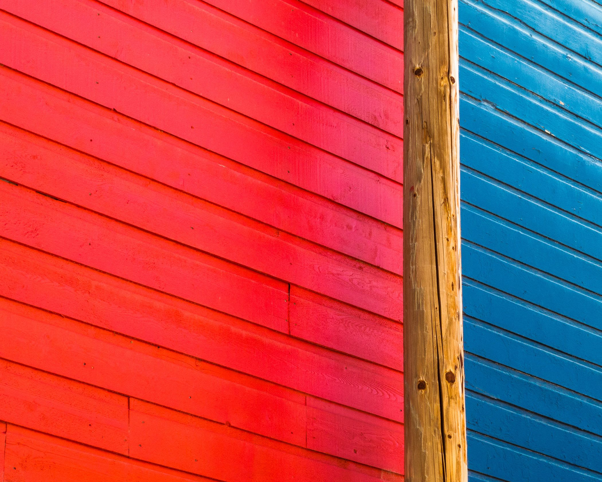 A red and blue wall separated by a telephone pole