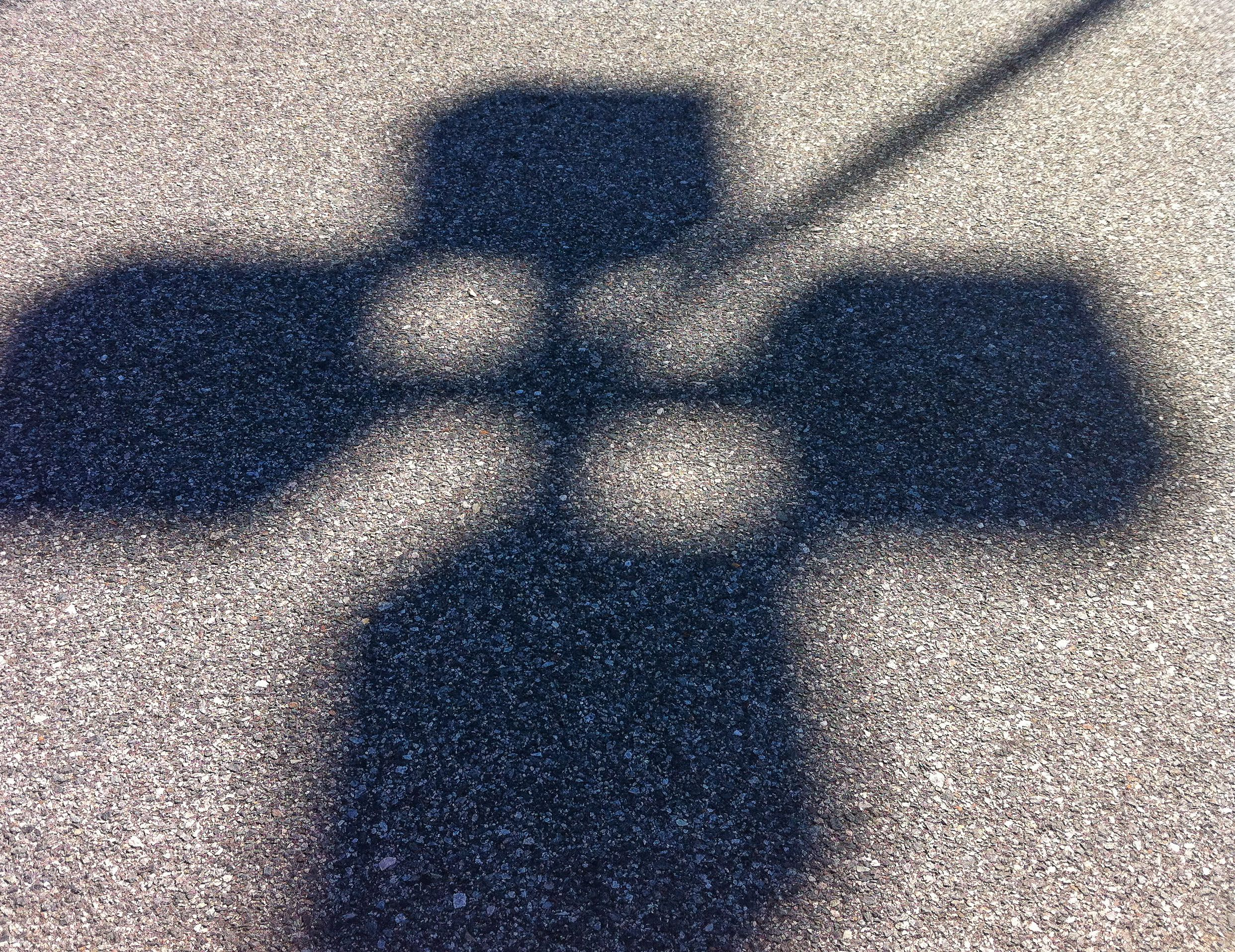 The shadow of a light pole on concrete